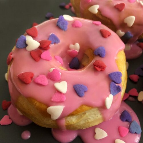 valentine donut on a plate with heart sprinkles