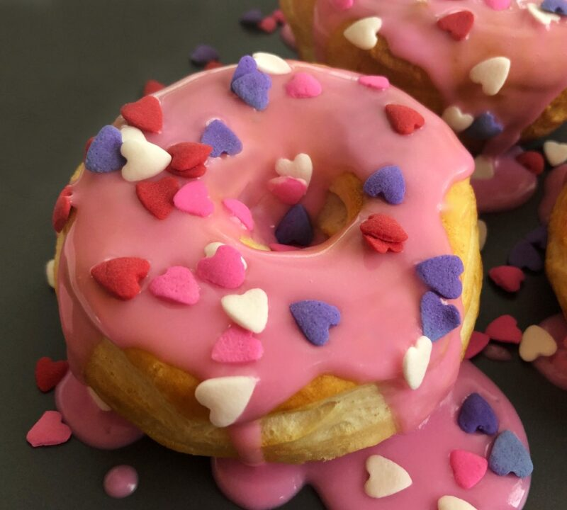 valentine's day donuts on a plate with heart sprinkles and a pink glaze