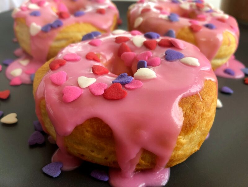 Valentine air fryer donuts with a pink glaze and heart sprinkles