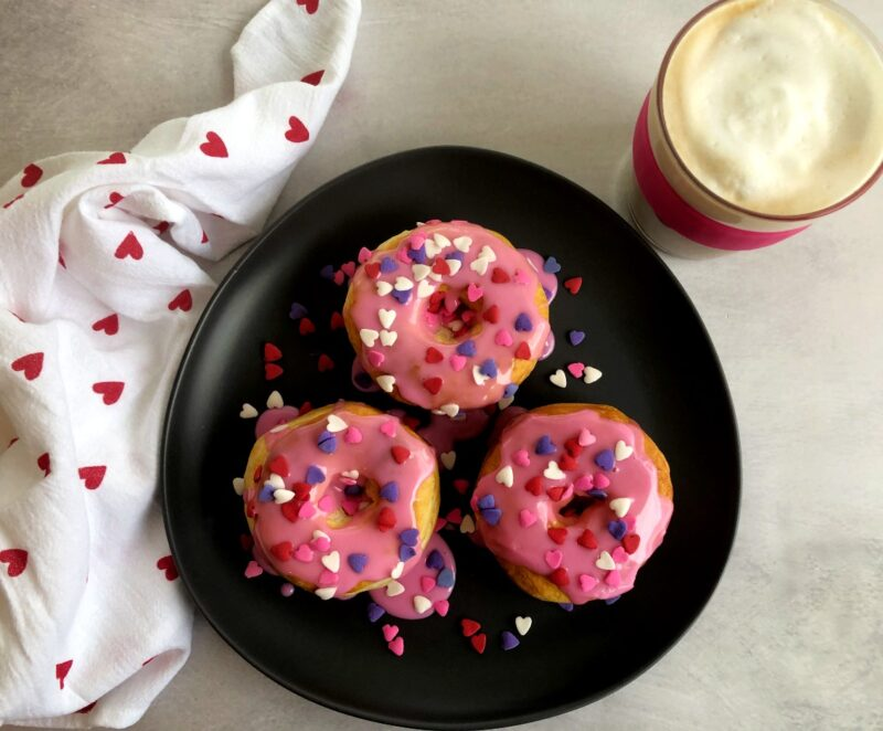 valentine donuts on a plate with a latte and a heart napkin