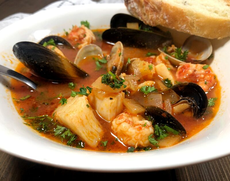 a bowl of seafood cioppino with mussels, clams, shrimp, fish, and scallops served with bread
