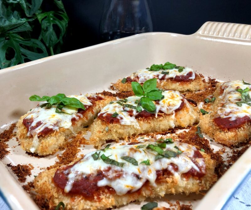 baked marinara chicken in a baking dish topped with cheese and fresh basil