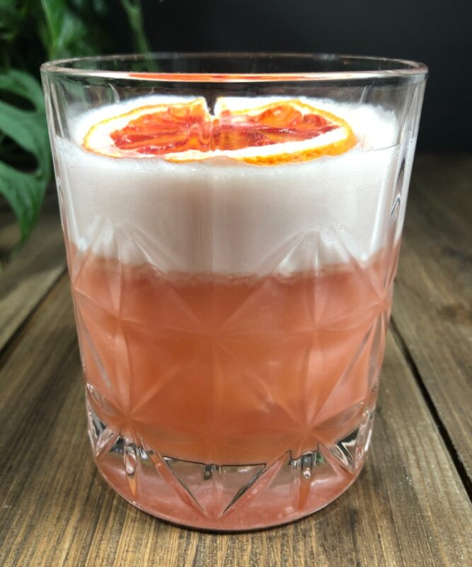 blood orange whiskey cocktail in a low ball glass garnished with an orange slice