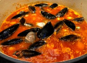 cioppino in a pot with seafood added