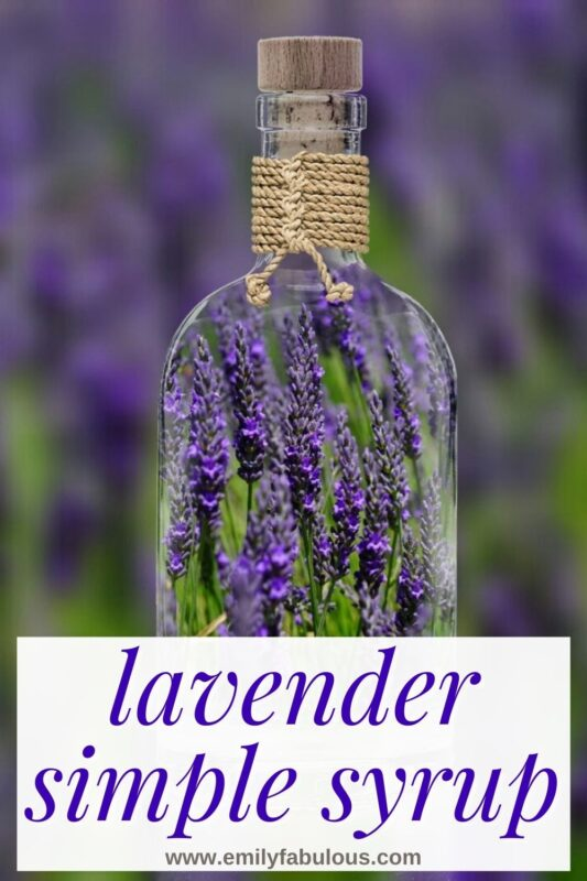 a glass bottle with lavender inside in front of a field of lavender