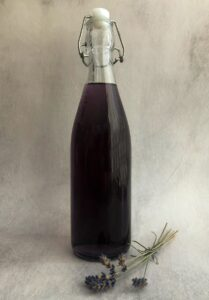 lavender syrup in a bottle with a sprig of dried lavender