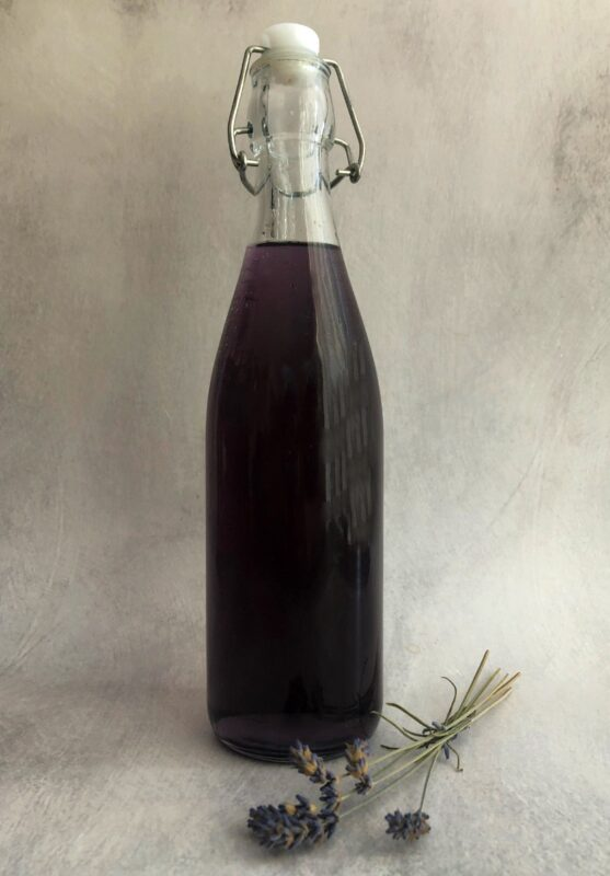 a flip top bottle with purple lavender syrup and a sprig of dried lavender