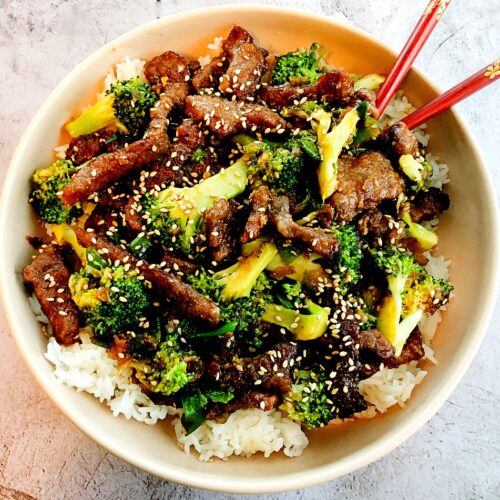 sticky beef, broccoli and rice in a bowl with chopsticks