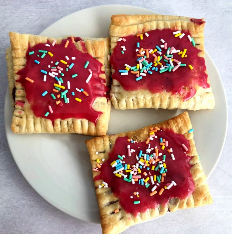 three triple berry pop tarts with sprinkles on a plate