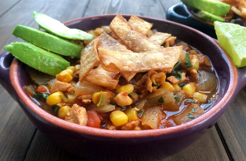 a bowl of tortilla soup with fried tortillas strips and avocado on top