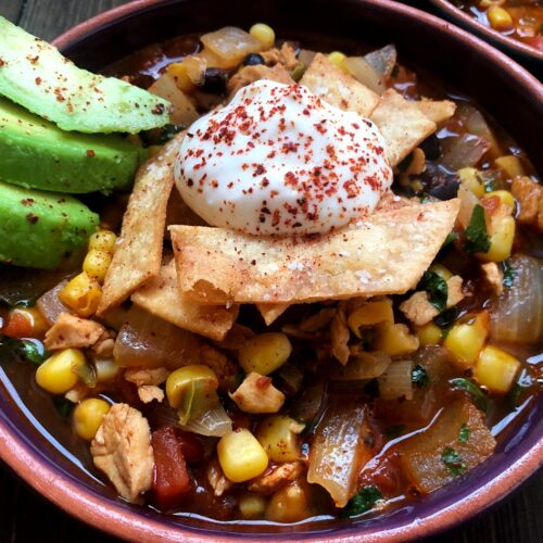 bowl of tortilla soup with avocado and sour cream