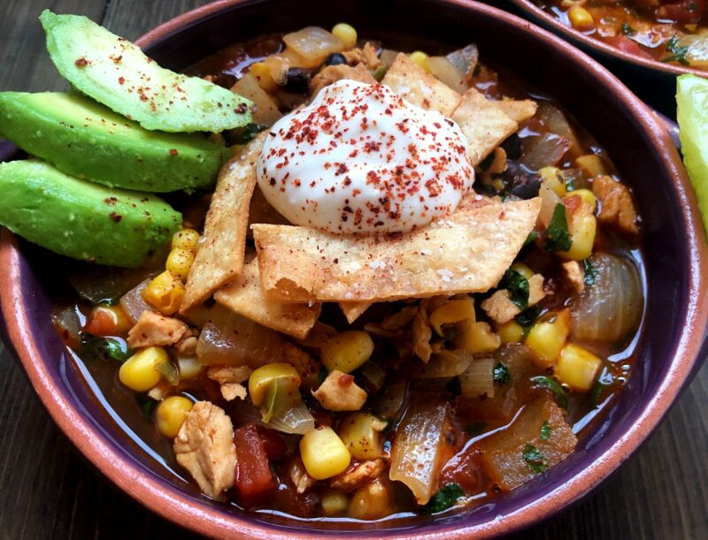 bowl of tortilla soup with avocado and sour cream on top