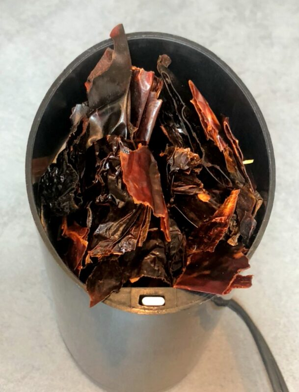 dried, cut up Mexican chiles in a grinder