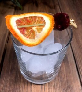 empty cocktail glass with an orange and cherry garnish