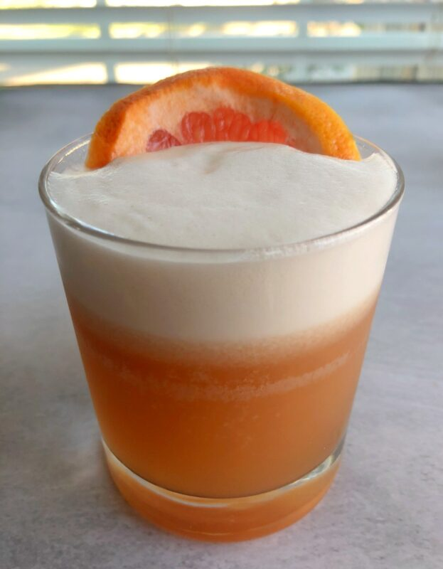 a grapefruit pisco sour in a lowball glass with a slice of grapefruit on top