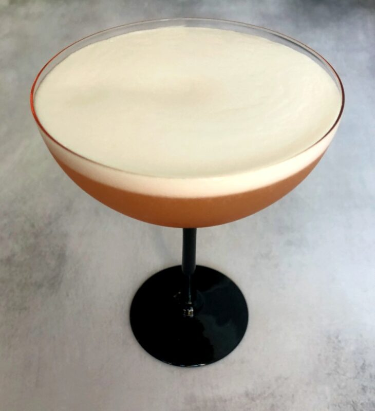 a grapefruit pisco sour cocktail with egg white foam in a coupe glass