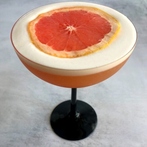 grapefruit pisco sour with grapefruit slice on top