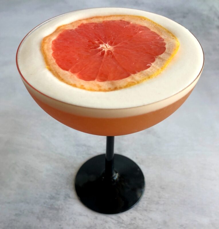 a grapefruit pisco sour drink with a grapefruit slice on top of the egg white foam