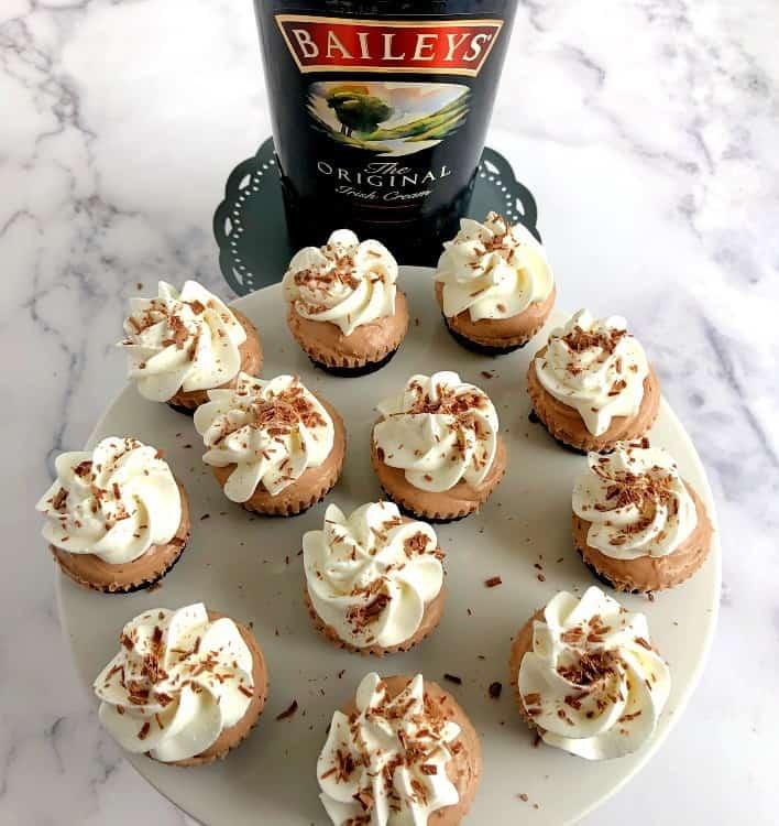 mini irish cream cheesecakes and a bottle irish cream liqueur