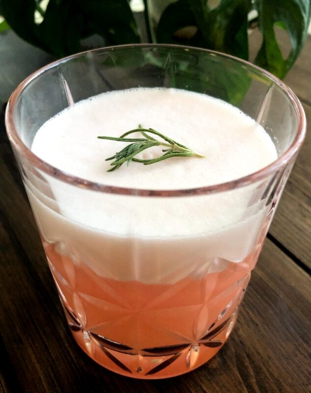 rosemary grapefruit vodka cocktail with rosemary garnish on top of foam