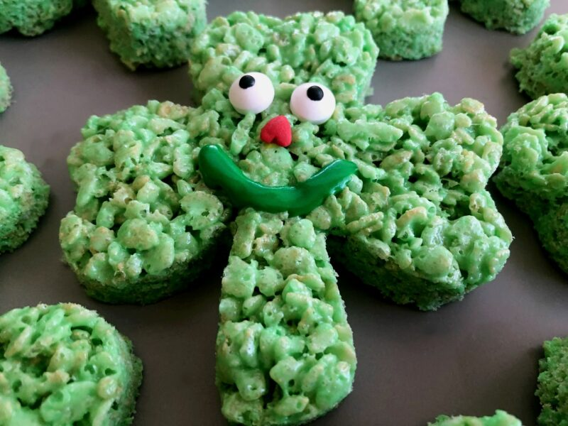 shamrock rice krispie treat with a frosting and sprinkle face
