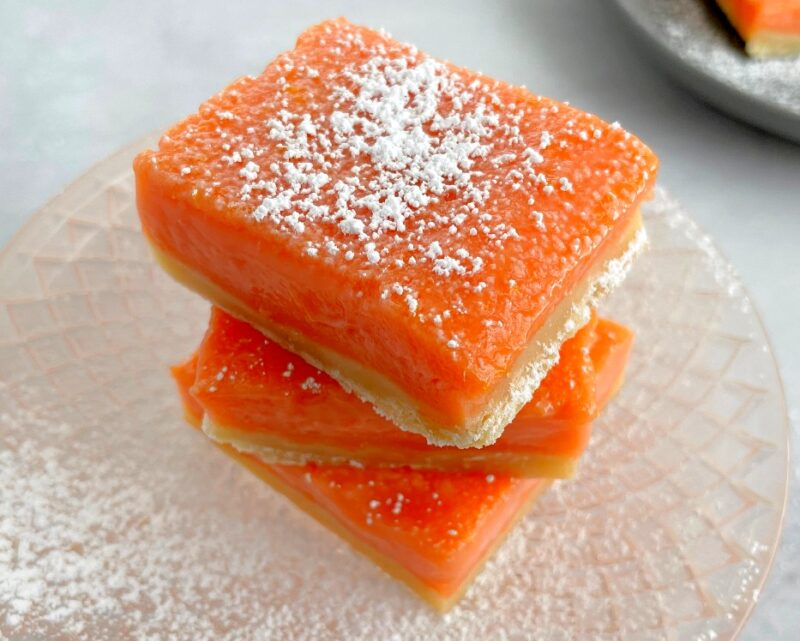 stacked grapefruit bars with powdered sugar on top