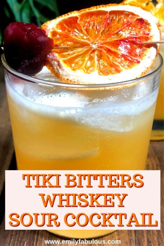 whiskey sour made with tiki bitters in a cocktail glass with a fruit garnish