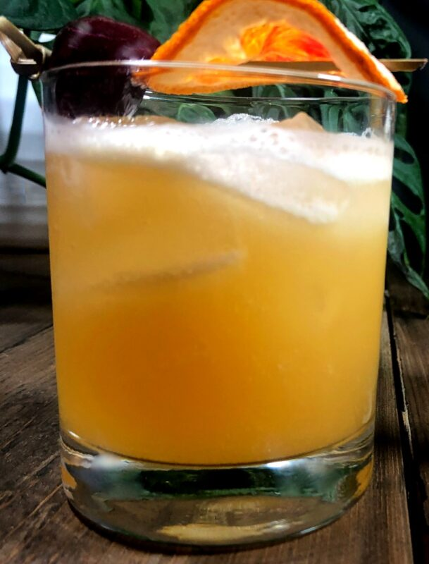 whiskey tiki bitters cocktail with an orange slice and a cherry