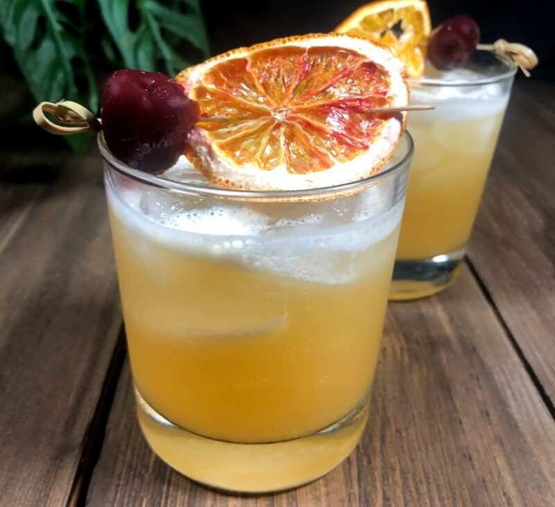 whiskey tiki bitters cocktails with orange and cherry as garnish