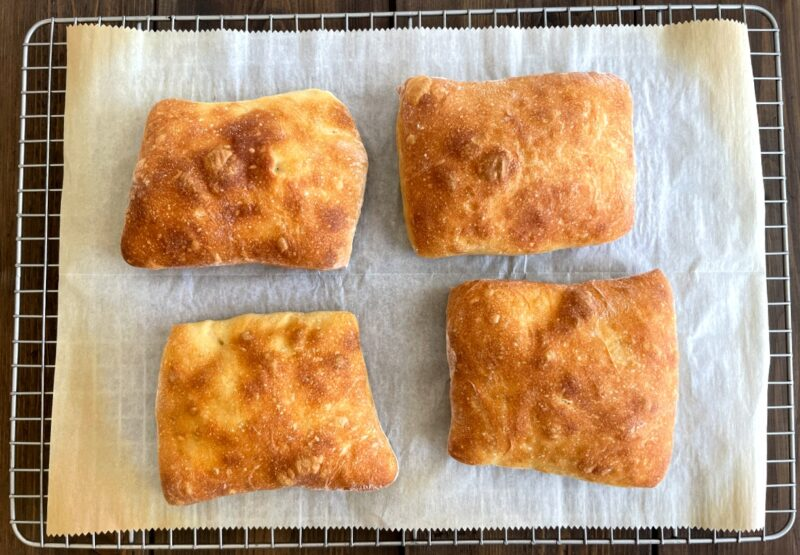 four baked ciabatta rolls on a cooling rack