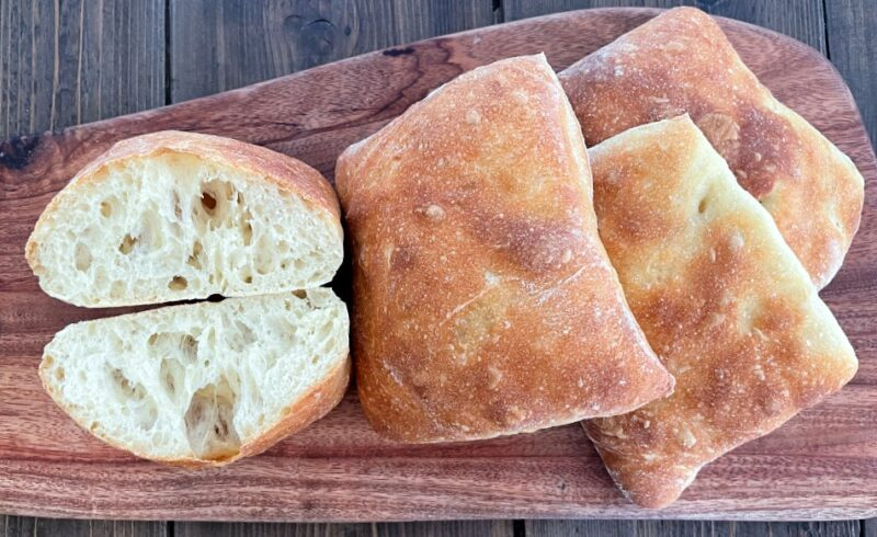 ciabatta rolls on a cutting board, oe cut in half