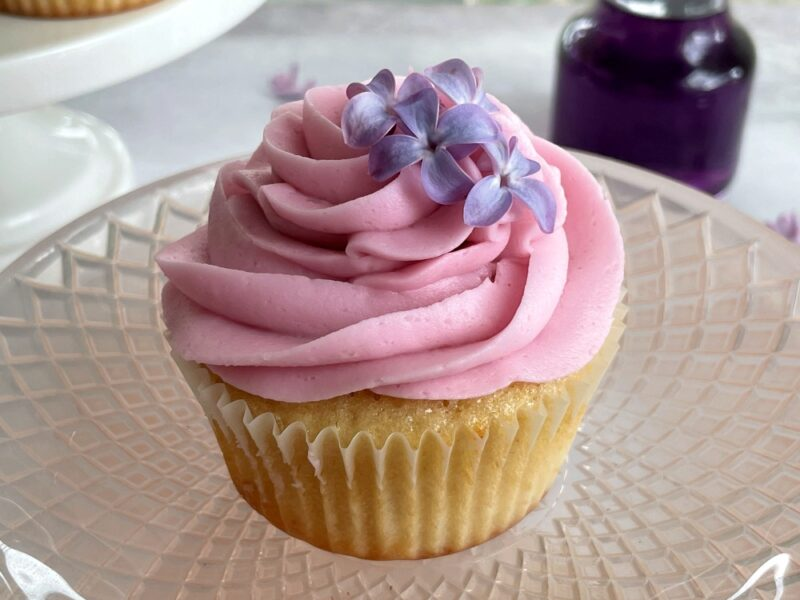a lilac cupcake on a pink platter
