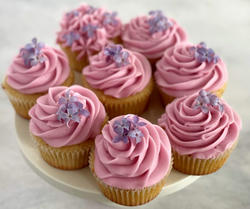 8 lilac cupcakes with fresh lilac flowers on top