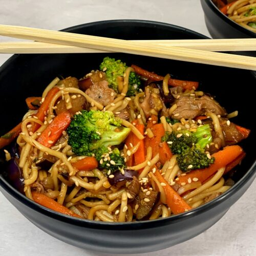 a bowl of udon noodles with beef and vegetables