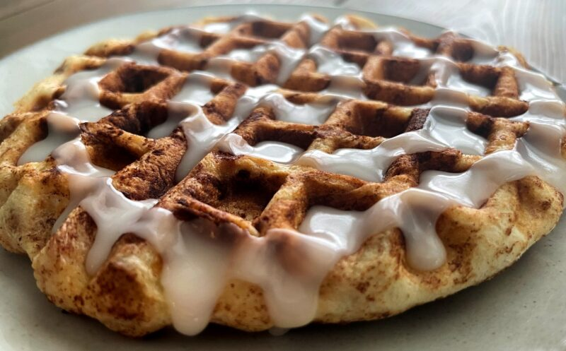 cinnamon roll cooked in a waffle maker with frosting on top
