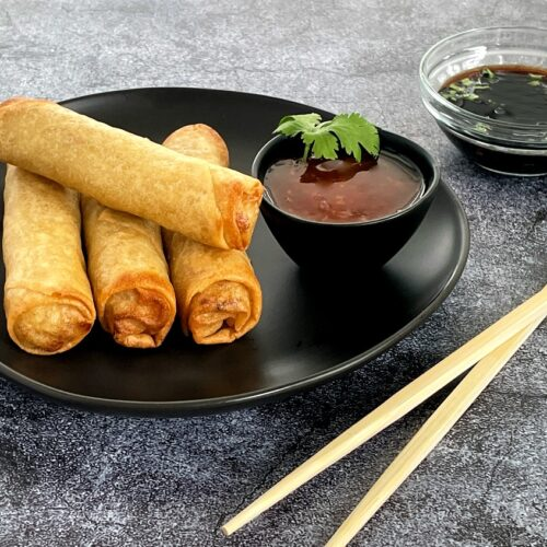 spring rolls on a plate with chili sauce and soy sauce on the side