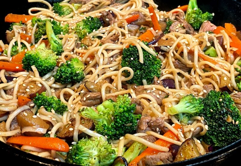 udon noodle stir fry in a cast iron pan