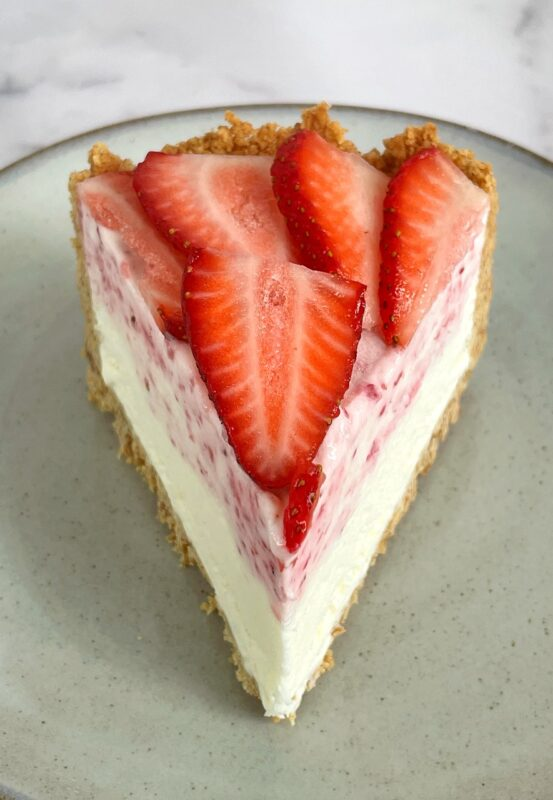 a slice of strawberry ice cream cheesecake pie with fresh strawberries on top