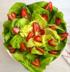 butter lettuce and strawberries in a bowl