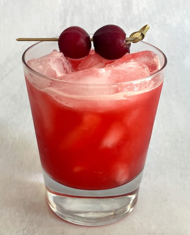a cherry margarita on ice with two cherries as garnish