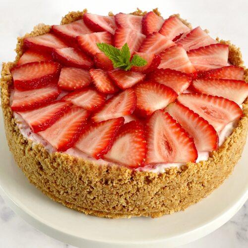 strawberry ice cream cheesecake pie with sliced fresh strawberries on top