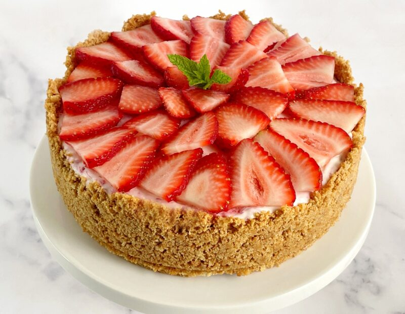 strawberry ice cream cheesecake with sliced fresh strawberries on top