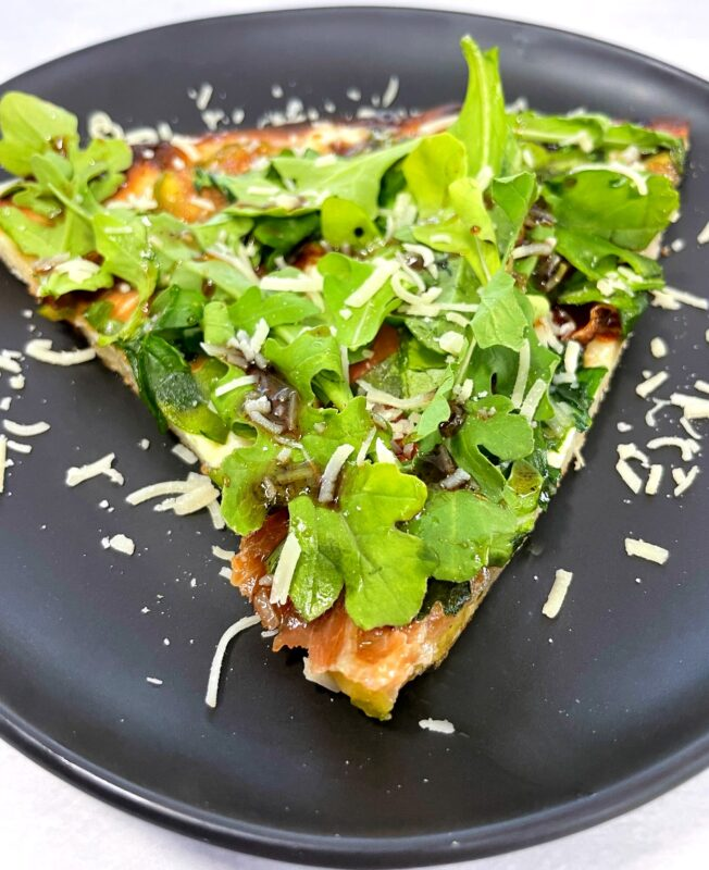 a slice of fig and prosciutto pizza with arugula on top