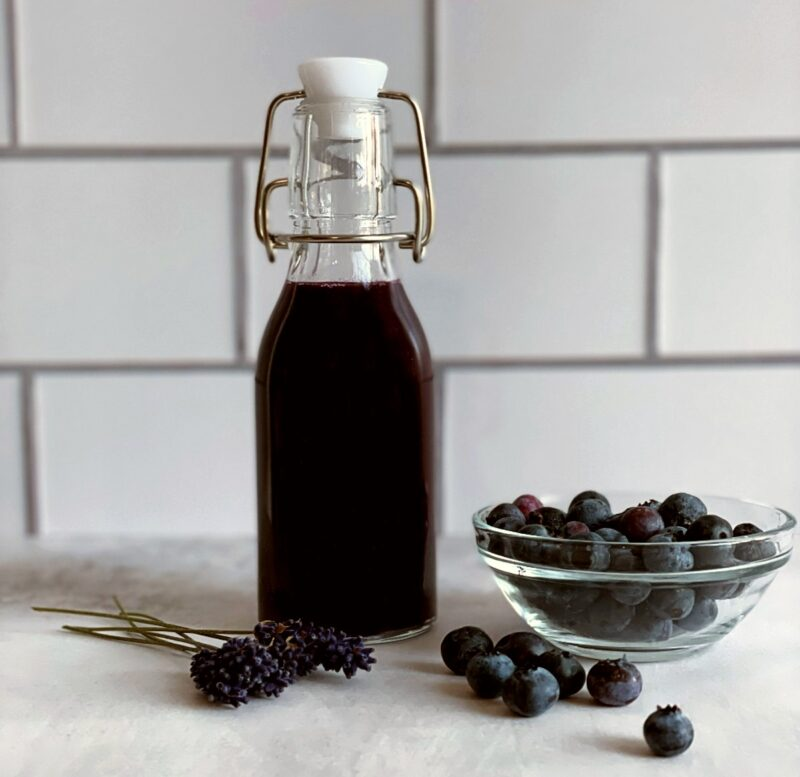 blueberry lavender syrup, a bowl of fresh blueberries and fresh lavender sprigs