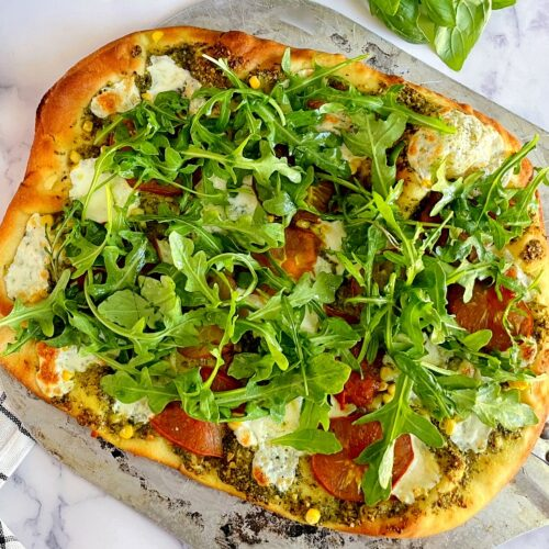 garden veggie pesto pizza on a pizza peel