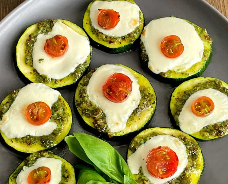 pesto zucchini bites on a plate with fresh basil cooked in the air fryer