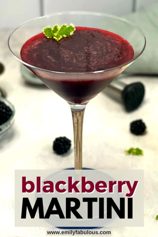 a blackberry martini in a martini glass with a muddler on the side