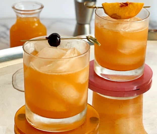 peach bourbon sours on a tray