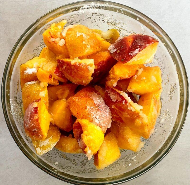 sliced peach and sugar in a bowl