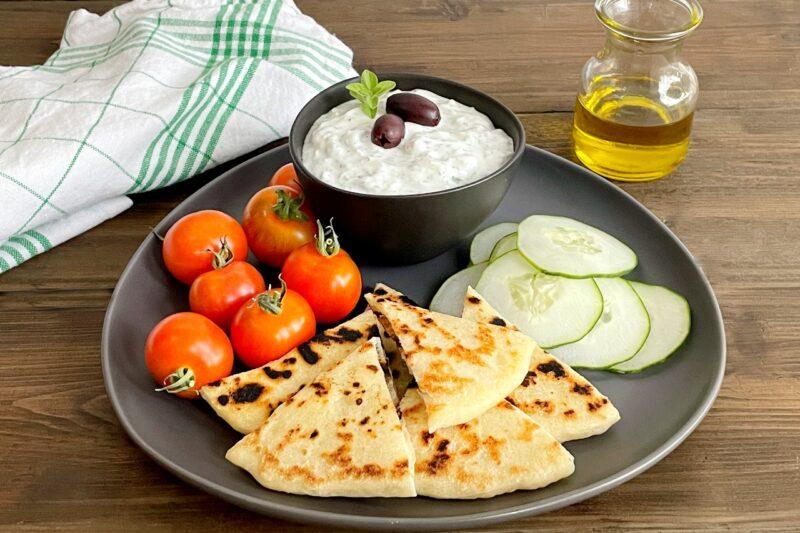 tzatziki sauce with veggies and pita on a plate